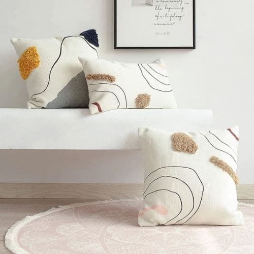 three white abstract cushion covers