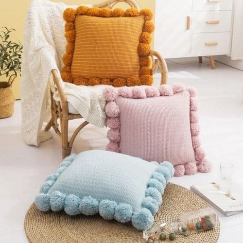 three cushion covers with pom poms