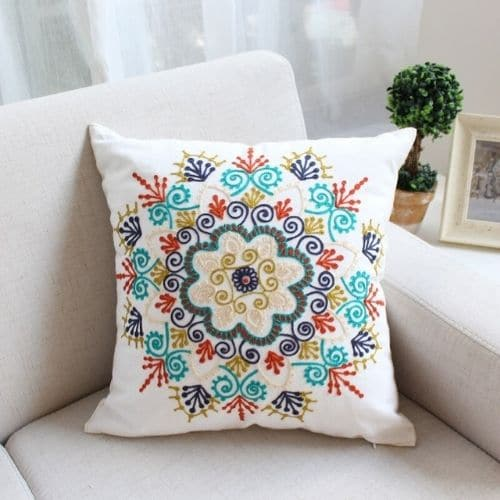 one white embroidered cushion cover