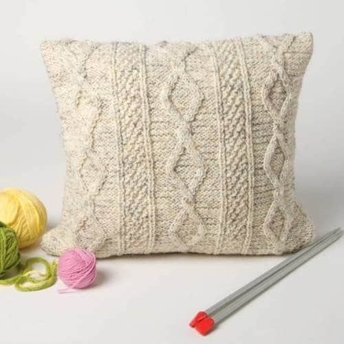 one white knitted cushion cover