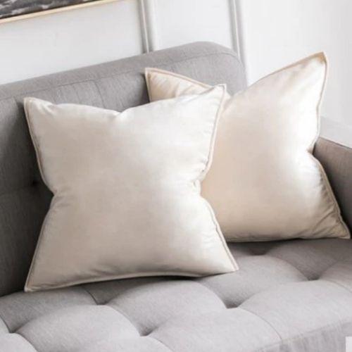 two cream cushion covers